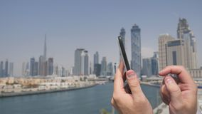 Un hombre imprime un mensaje en el teléfono en el fondo del panorama de Dubai Primer de la mano almacen de metraje de vídeo