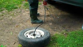 Un hombre infla una rueda de coche vieja con un compresor almacen de metraje de vídeo