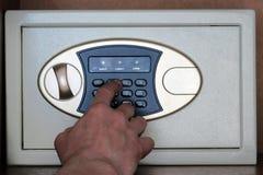 Un hombre inscribe la cerradura de combinaci?n en la caja fuerte en la oficina Almacenamiento seguro del primer del dinero, joyer fotos de archivo libres de regalías