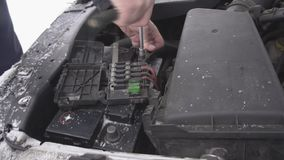 Un hombre instala una batería de coche y aprieta el terminal, invierno, nieve, descarga de la batería, primer, cámara lenta, come metrajes