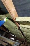 Un hombre instala una capa del aislamiento térmico de un tejado termal - usando los paneles de lanas minerales, montándolo entr fotografía de archivo libre de regalías