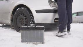 Un hombre instala una nueva batería en el coche en el invierno, él está nevando, cámara lenta metrajes
