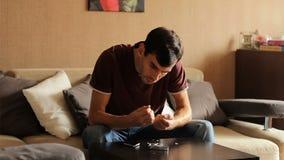 Un hombre joven acaba mis clavos acortados Corte quita los clavos de la tabla manicura del ` s de los hombres almacen de video