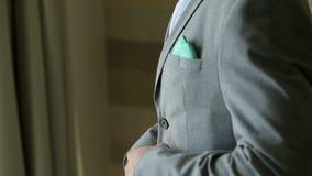 Un hombre joven acertado sujeta los botones en su situación de la chaqueta cerca de la ventana metrajes