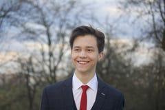 Un hombre joven, adolescente, en un traje clásico El caminar a lo largo de las avenidas del parque de la primavera Imagen de archivo libre de regalías
