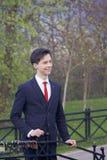 Un hombre joven, adolescente, en un traje clásico El caminar a lo largo de las avenidas del parque de la primavera Fotos de archivo libres de regalías