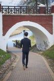 Un hombre joven, adolescente, en un traje clásico El caminar a lo largo de las avenidas del parque de la primavera Fotos de archivo