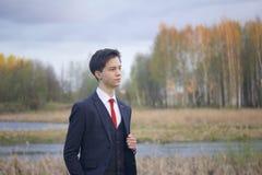 Un hombre joven, adolescente, en un traje clásico El caminar a lo largo de las avenidas del parque de la primavera Fotografía de archivo libre de regalías