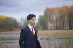 Un hombre joven, adolescente, en un traje clásico El caminar a lo largo de las avenidas del parque de la primavera Imagen de archivo