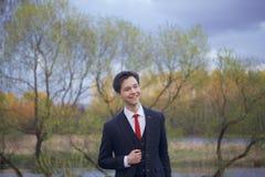 Un hombre joven, adolescente, en un traje clásico El caminar a lo largo de las avenidas del parque de la primavera Imágenes de archivo libres de regalías