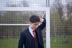 Un hombre joven, adolescente, en un traje clásico Está en la meta del fútbol Él se inclinó contra la barra con su mano, y puso su Fotografía de archivo libre de regalías