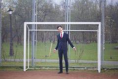 Un hombre joven, adolescente, en un traje clásico Está en la meta del fútbol, se separó las manos Foto de archivo libre de regalías