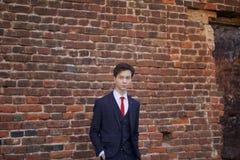 Un hombre joven, adolescente, en un traje clásico La reflexión se está colocando delante de la pared vieja del ladrillo rojo, pon Imagen de archivo