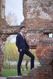 Un hombre joven, adolescente, en un traje clásico La reflexión se está colocando delante de la pared vieja del ladrillo rojo, pon Imágenes de archivo libres de regalías