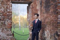 Un hombre joven, adolescente, en un traje clásico La reflexión se está colocando delante de la pared vieja del ladrillo rojo, pon Fotografía de archivo libre de regalías