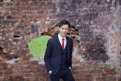 Un hombre joven, adolescente, en un traje clásico La reflexión se está colocando delante de la pared vieja del ladrillo rojo, pon Fotos de archivo libres de regalías