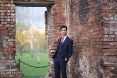 Un hombre joven, adolescente, en un traje clásico Se coloca absurdo enfrente de la pared vieja del ladrillo rojo, poniendo sus ma Imagenes de archivo