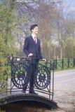 Un hombre joven, adolescente, en un traje clásico Se coloca en el puente del vintage en el parque, poniendo sus manos en la verja Fotografía de archivo