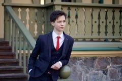 Un hombre joven, adolescente, en un traje clásico Se coloca, inclinándose en la verja de una escalera de madera Fotografía de archivo libre de regalías