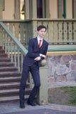 Un hombre joven, adolescente, en un traje clásico Se coloca, inclinándose en la verja de una escalera de madera Fotos de archivo