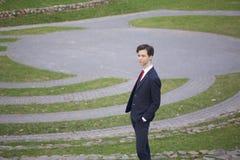 Un hombre joven, adolescente, en un traje clásico Se coloca en los pasos de piedra del anfiteatro del verano, poniendo sus manos  Fotografía de archivo