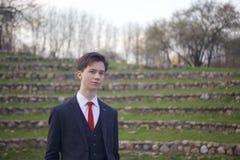 Un hombre joven, adolescente, en un traje clásico Se coloca en los pasos de piedra del anfiteatro del verano, poniendo sus manos  Imagenes de archivo