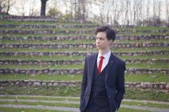 Un hombre joven, adolescente, en un traje clásico Se coloca en los pasos de piedra del anfiteatro del verano, poniendo sus manos  Foto de archivo