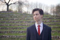 Un hombre joven, adolescente, en un traje clásico Se coloca en los pasos de piedra del anfiteatro del verano, poniendo sus manos  Imágenes de archivo libres de regalías