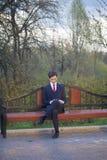 Un hombre joven, adolescente, en un traje clásico Se sienta en un banco del vintage en un parque de la primavera Él sostiene un s Foto de archivo libre de regalías