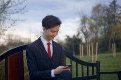 Un hombre joven, adolescente, en un traje clásico Se sienta en un banco del vintage en un parque de la primavera Él sostiene un s Imágenes de archivo libres de regalías