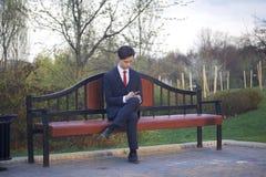 Un hombre joven, adolescente, en un traje clásico Se sienta en un banco del vintage en un parque de la primavera Él sostiene un s Imagen de archivo