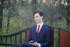 Un hombre joven, adolescente, en un traje clásico Se sienta en un banco del vintage en un parque de la primavera Él sostiene un s Fotos de archivo libres de regalías