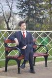 Un hombre joven, adolescente, en un traje clásico Se sienta en un banco del vintage en un parque de la primavera Fotografía de archivo libre de regalías