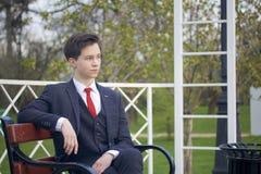 Un hombre joven, adolescente, en un traje clásico Se sienta en un banco del vintage en un parque de la primavera Imágenes de archivo libres de regalías