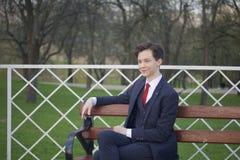Un hombre joven, adolescente, en un traje clásico Se sienta en un banco del vintage en un parque de la primavera Fotografía de archivo