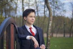 Un hombre joven, adolescente, en un traje clásico Se sienta en un banco del vintage en un parque de la primavera Fotos de archivo