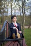 Un hombre joven, adolescente, en un traje clásico Se sienta en un banco del vintage en un parque de la primavera Imagenes de archivo