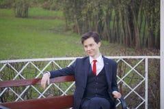 Un hombre joven, adolescente, en un traje clásico Se sienta en un banco del vintage en un parque de la primavera Fotos de archivo libres de regalías