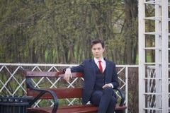 Un hombre joven, adolescente, en un traje clásico Se sienta en un banco del vintage en un parque de la primavera Imagen de archivo