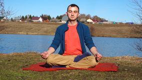 Un hombre joven apuesto que hace yoga en un embarcadero con el contexto tropical de la isla metrajes