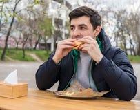 Un hombre joven arranca con los dientes una hamburguesa en un snack bar Fotografía de archivo