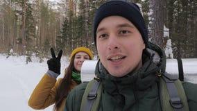 Un hombre joven, blogger video, está registrando un vídeo en el bosque con su novia almacen de metraje de vídeo