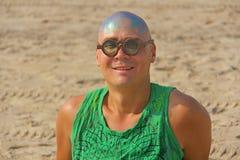 Un hombre joven calvo e inusual, un monstruo, con una cabeza calva brillante y vidrios de madera redondos en el fondo de la playa imágenes de archivo libres de regalías