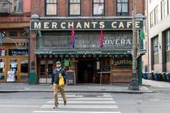 Un hombre joven camina delante del café de los comerciantes, la barra más vieja de Seattle, Washington, los E.E.U.U. fotografía de archivo libre de regalías