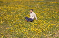 Un hombre joven, campo de flor que se sienta, outodoors, día soleado Foto de archivo