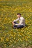 Un hombre joven, campo de flor que se sienta, outodoors, día soleado Imagen de archivo