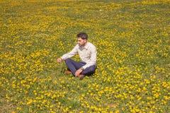 Un hombre joven, campo de flor que se sienta, outodoors, día soleado Foto de archivo libre de regalías