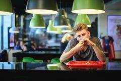 Un hombre joven codicioso come una gran hamburguesa apetitosa que se sienta en un restaurante de los alimentos de preparación ráp Fotos de archivo