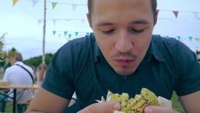 Un hombre joven come una hamburguesa o un cheeseburger con un bollo verde en un café al aire libre en un festival o una feria del almacen de metraje de vídeo