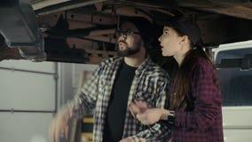 Un hombre joven comparte la experiencia de mantener y de reparar un coche con un recién llegado de la muchacha como mecánico de a almacen de video